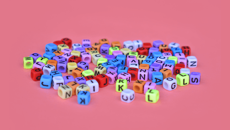 Coloured letters scattered on a red background