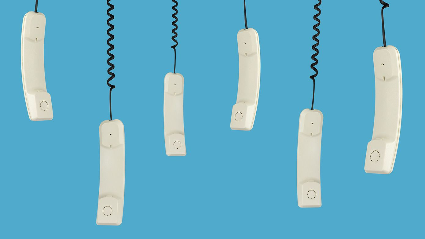 Corded phones hanging on a blue background